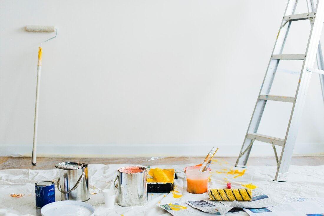 Leiter und Malerutensilien vor einer weißen Wand